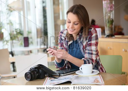 Brunette girl sending text message with smartphone
