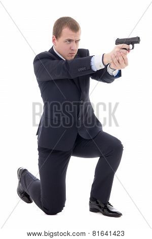 Man In Business Suit Sitting On Knee And Shooting With Gun Isolated On White