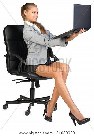 Businesswoman on office chair, holding laptop in her arms at eye level