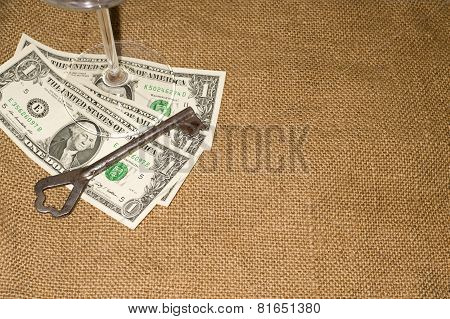 Glass,old Key And A Few Us Dollars Banknotes On The Old Tissue