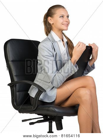 Businesswoman sitting on office chair with clipbord in hands, looking ahead, smiling