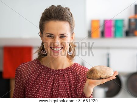 Portrait Of Happy Young Housewife Showing Mushroom