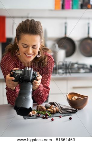 Happy Female Food Photographer Checking Photos In Camera