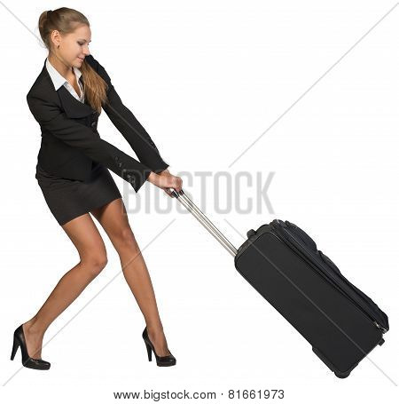 Businesswoman dragging heavy wheeled suitcase with both hands