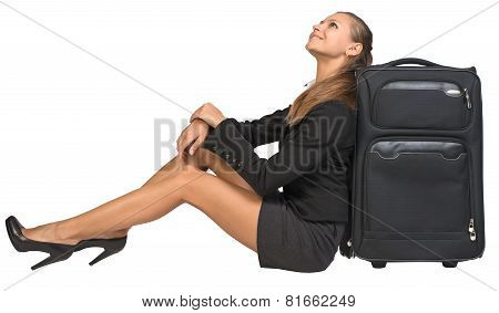 Businesswoman sitting next to front view suitcase, looking upwards, smiling