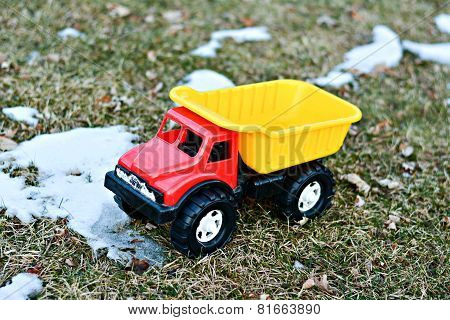 Child dump truck on thawing grass