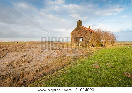Wet Stubble Field And An Abandoned Small Building