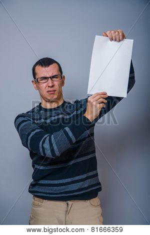 European-looking man of 30 years holding a blank sheet, resentme