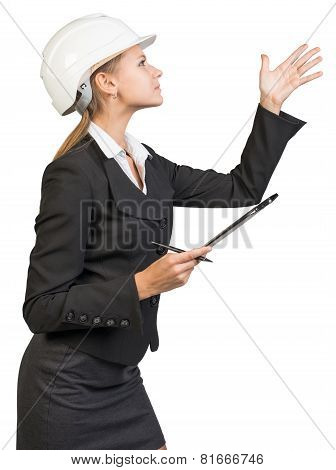 Businesswoman wearing hard hat, with clipboard and pen, pointing at something