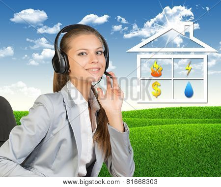 Businesswoman in headset, symbols of public utilities beside
