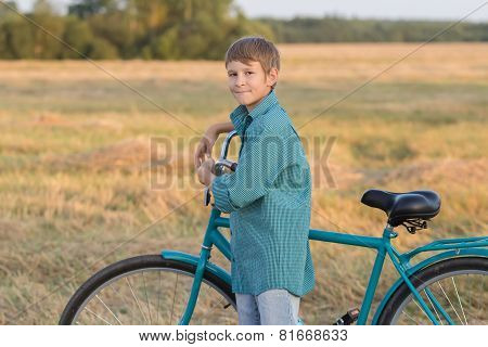 Teenager Boy With Bicycle In Sunset Farm Field