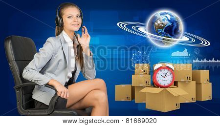 Businesswoman in headset, Globe, commodity boxes and alarm-clock beside