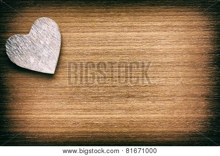 Wooden heart on a faded grunge wooden background
