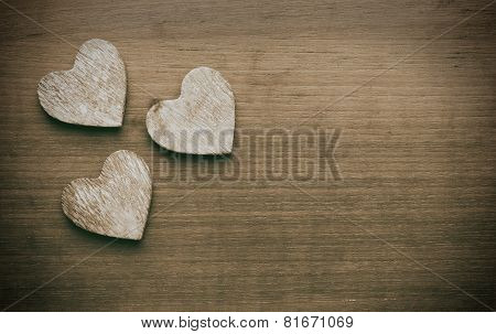 Three wooden hearts on a grungy wooden background