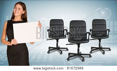 Businesswoman holding blank paper sheet. Office chairs beside. Hi-tech graphs as backdrop