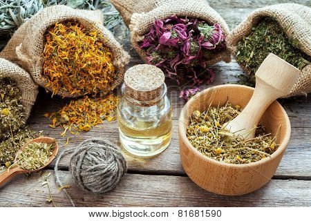 Healing Herbs In Hessian Bags, Mortar With Chamomile And Essential Oil On Wooden Table, Herbal Medic