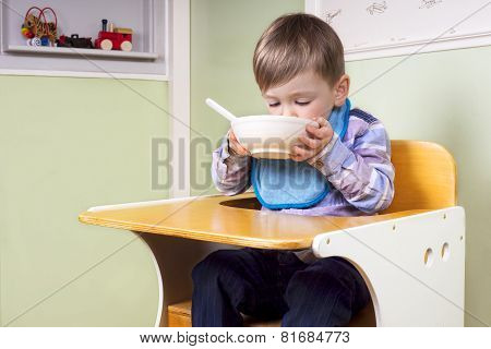 Cute Little Boy Eating From A Bowl
