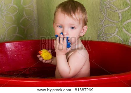 Beautiful little blond girl sitting in the bathroom and chew toys