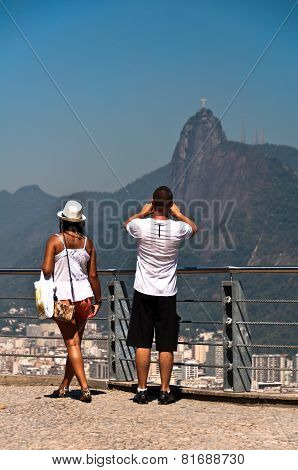 Couple photographing Christ the Redeemer in Rio de Janeiro, Brazil