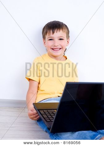 Litle Boy With Laptop On The Floor Near The Wall