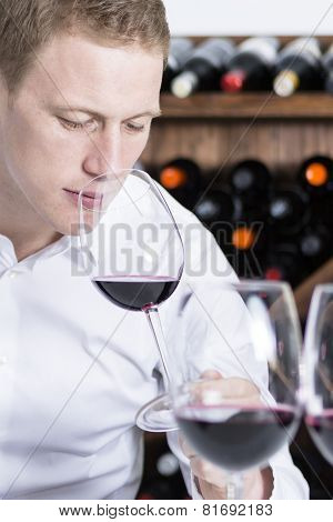 Male Winemaker Smelling A Red Wineglass.