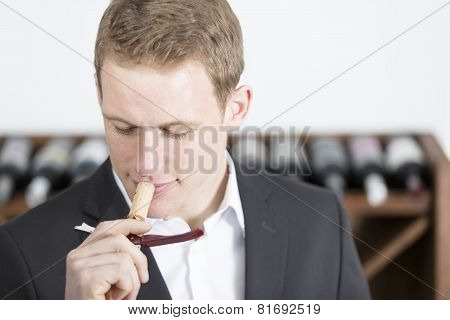 Man Smelling A Cork Stopper.