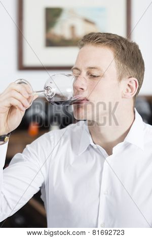 Man Tasting A Glass Of Red Wine.