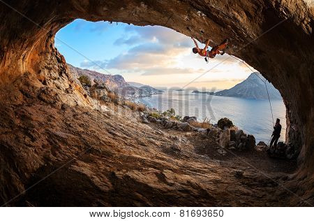Young woman lead climbing in cave