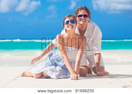 young happy couple sitting on tropical beach. honeymoon concept