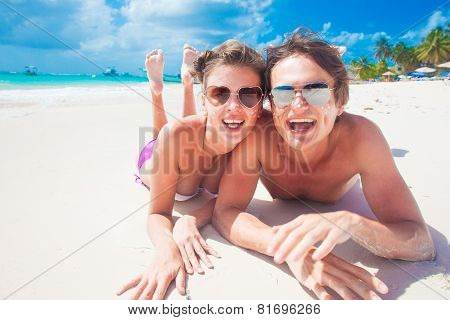 portrait of happy young couple with suncream dots at beac