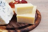 picture of brie cheese  - edam parmesan and brie cheese on wooden platter over wooden table - JPG