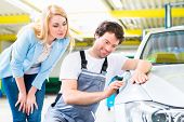 stock photo of scratch  - Male mechanic examine car finish on dents or scratches in workshop  - JPG