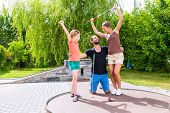 picture of miniature golf  - Family playing miniature golf outdoors - JPG