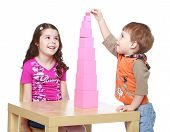 stock photo of montessori school  - Brother and sister collects Red Pyramid in the Montessori kindergarten - JPG