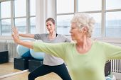 stock photo of stretching  - Two women doing stretching and aerobics workout at gym - JPG