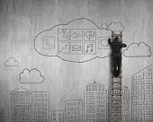 stock photo of wall cloud  - Businessman climbing and drawing cloud app icons doodles on concrete wall background - JPG