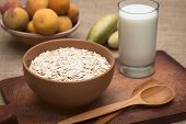 pic of oats  - Bowl full of rolled oats with a glass of milk and peaches in the back photographed with natural light  - JPG