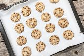 picture of baked raisin cookies  - Homemade chocolate chip cookie just baked on a tray over wooden background - JPG