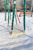 picture of snow-slide  - snow covered swing and slide at a playground in winter - JPG
