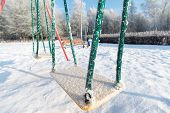 stock photo of snow-slide  - snow covered swing and slide at a playground in winter - JPG
