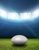 stock photo of generic  - A rugby stadium with a generic white rugby ball on a marked green grass pitch at night under illuminated floodlights - JPG