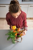foto of local shop  - Young housewife sort purchases after shopping on local market - JPG