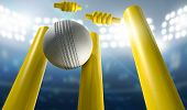 stock photo of cricket  - A white leather cricket ball hitting yellow wooden cricket wickets on a floodlit stadium background at night - JPG