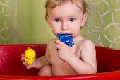 picture of soapy  - Babe blonde with soapy head playing with toys in the bathroom - JPG