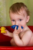 stock photo of soapy  - Babe blonde with soapy head playing with toys in the bathroom - JPG