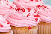picture of sprinkling  - Closeup of pink Valentines Day cupcakes with sprinkles shallow depth of field - JPG