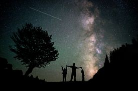 stock photo of cosmic  - Happy family father and boys silhouette with Milky Way and beautiful night sky full of stars in background - JPG
