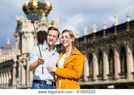 Tourist couple at Zwinger in Dresden taking selfie with phone on stick
