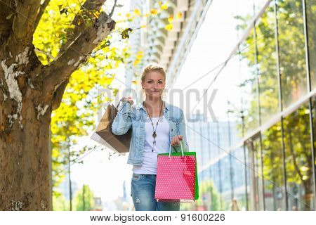 Girl walking down the street with shopping bags