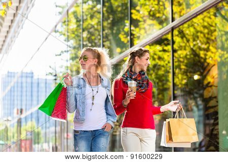 Two women friends walking down the street with shopping bags